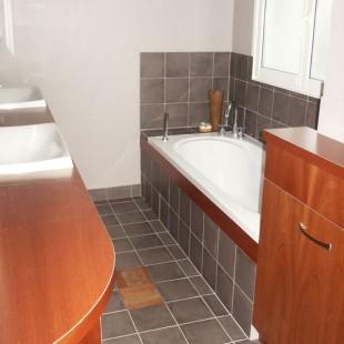 Quand le gris et le bois forment l'unité d'une salle de bains.